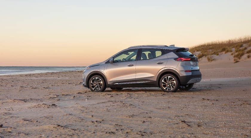A silver 2022 Chevy Bolt EUV is shown from the side parked on a beach at sunset.