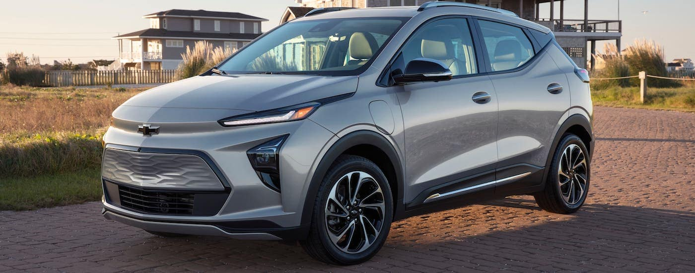 A silver 2022 Chevy Bolt EUV is parked in front of a beach house.