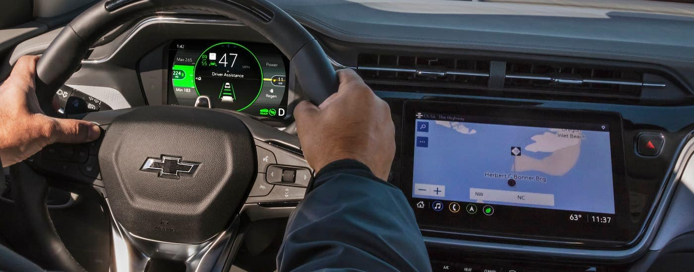 A closeup shows hands on a steering wheel and the infotainment center in a 2022 Chevy Bolt EUV.