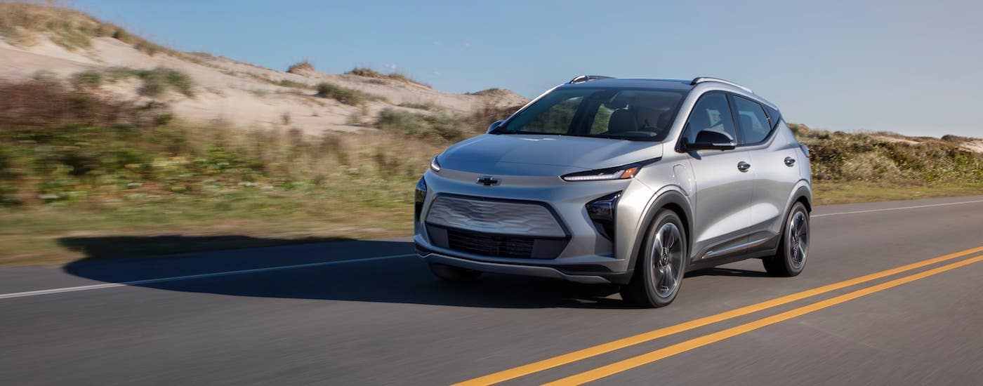 A silver 2022 Chevy Bolt EUV is driving in front of sand dunes.