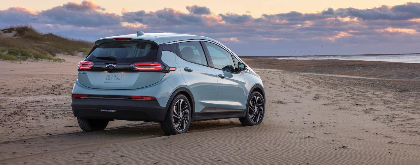 A pale blue 2022 Chevy Bolt EV is parked on a beach at sunset and shown from a rear angle.