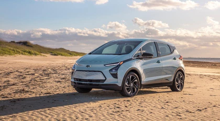 A pale blue/silver 2022 Chevy Bolt EV is parked on a beach.
