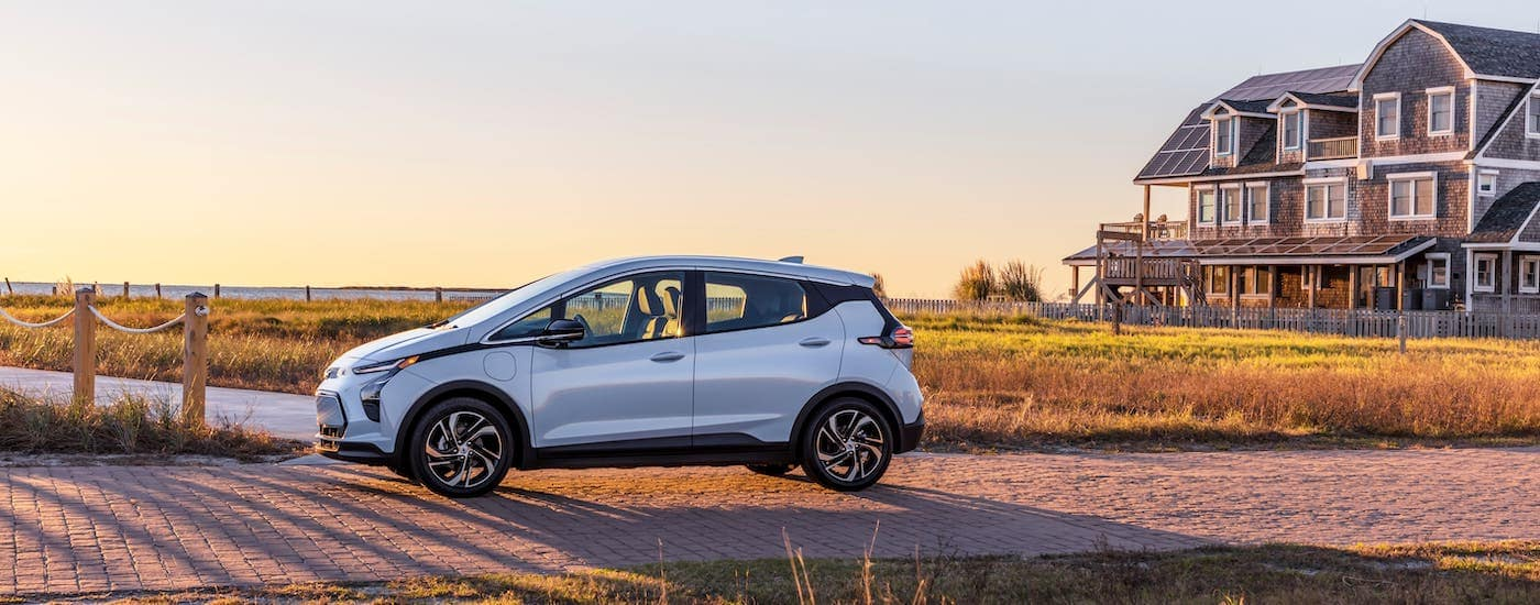 A pale blue 2022 Chevy Bolt EV is shown from the side while parked in front of a marsh and a mansion.