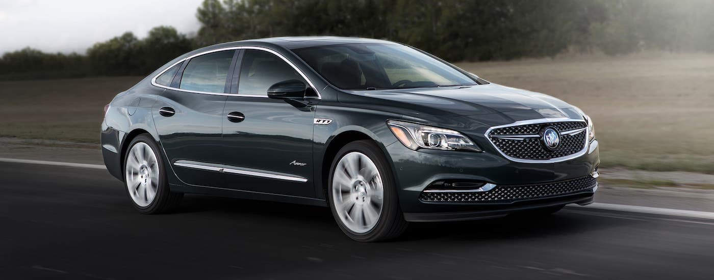 A black 2019 Buick LaCrosse Avenir is driving on a highway after leaving a Lexington used car dealer.