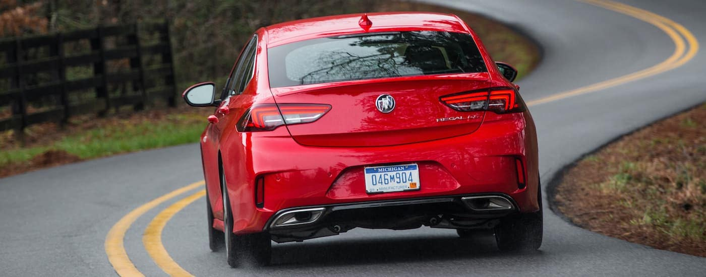 A red 2019 Buick Regal GS is shown from the rear driving down a winding road.