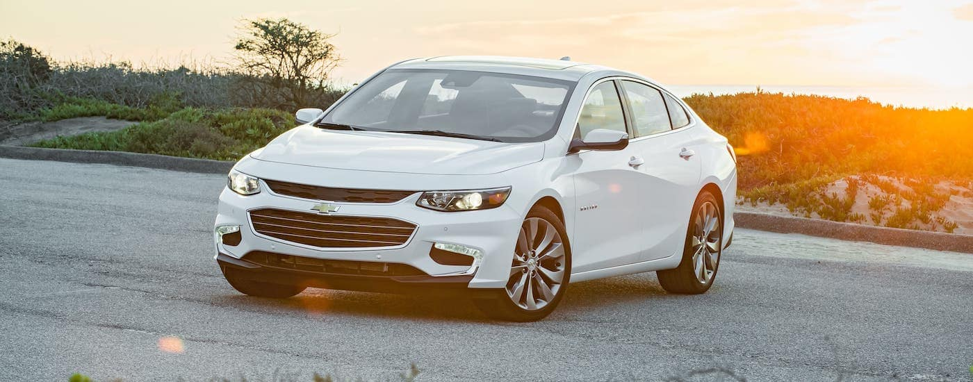 A white 2020 Chevy Malibu is parked in front of hills at sunset.