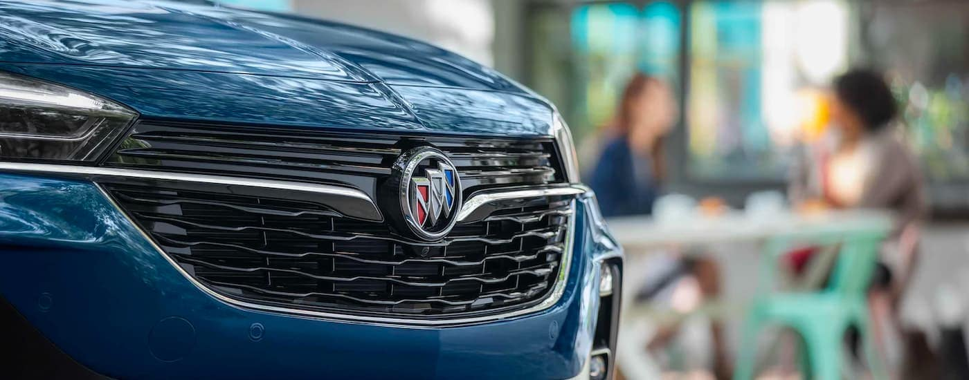 A close up shows the grille and Buick badge on a dark blue 2021 Buick Encore GX.