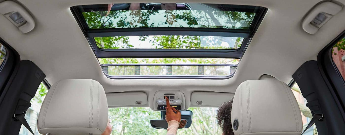 The moonroof is shown being opened in a 2021 Buick Encore GX.