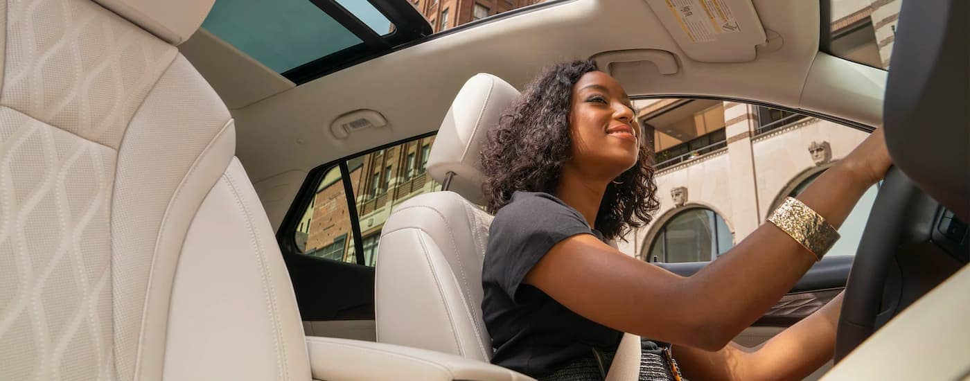 A girl is shown driving a 2021 Buick Envision.