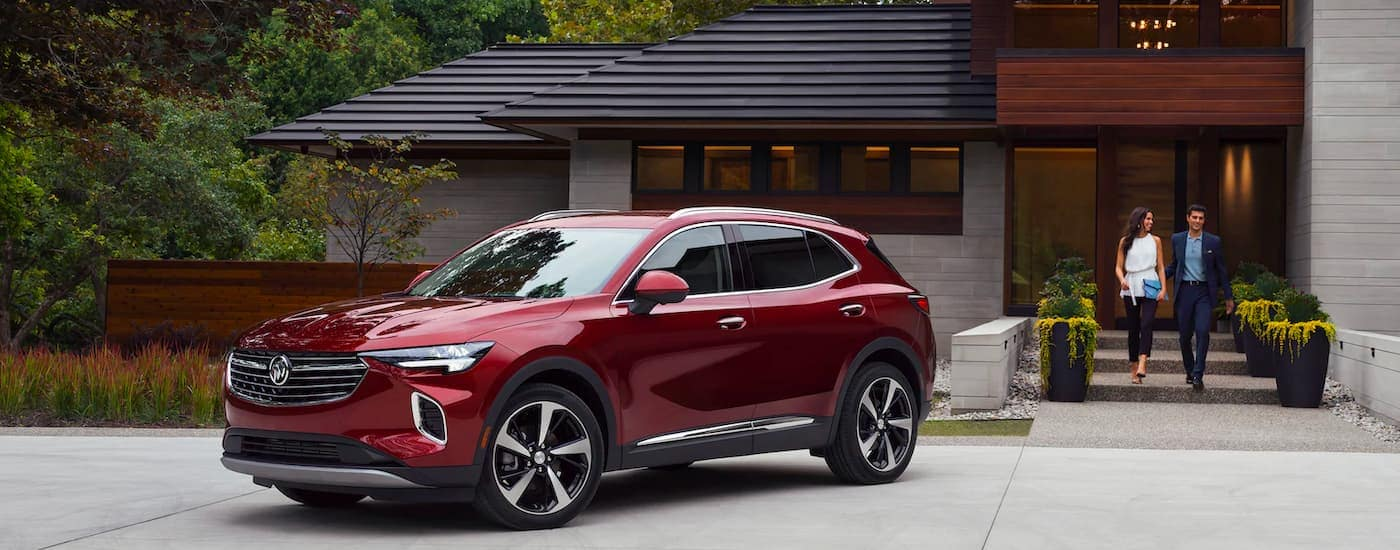 A red 2021 Buick Envision is angled right parked in a driveway after winning the 2021 Buick Envision vs 2021 Acura RDX comparison.