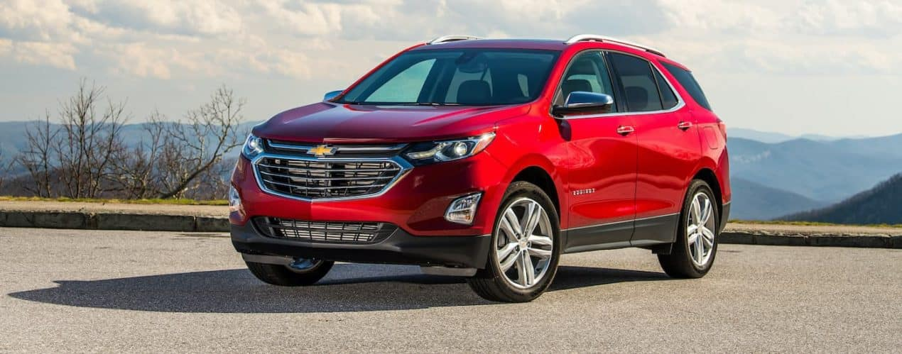 A red 2021 Chevy Equinox is shown parked in front of distant mountains after winning the 2021 Chevy Equinox vs 2021 Honda CR-V comparison.