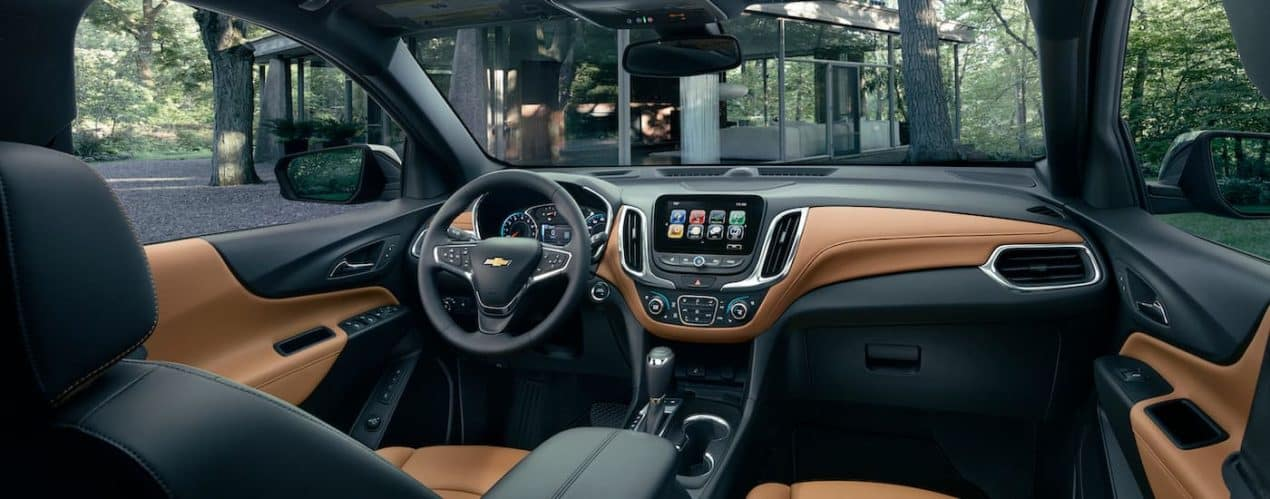 The brown and black interior is shown in a 2021 Chevy Equinox, overlooking a glass structure.