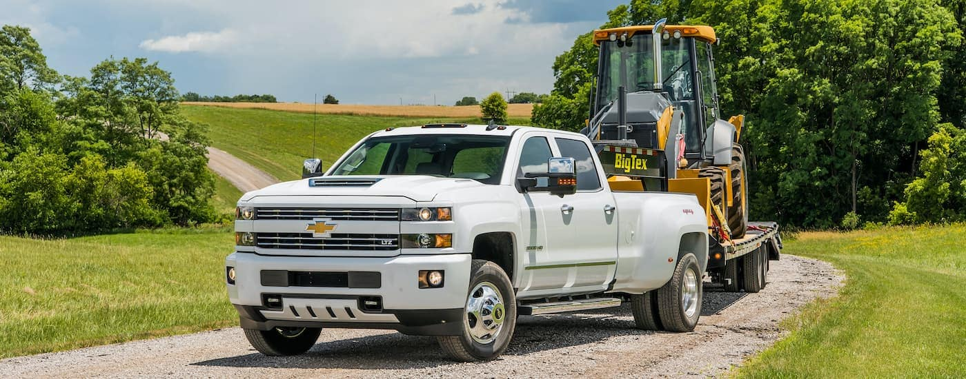 A white 2018 Chevy Silverado 3500HD LTZ is shown on a dirt path with a trailer and construction equipment.