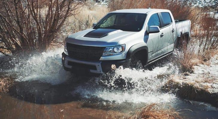 A silver 2019 Chevy Colorado ZR2 Bison is driving through water after leaving a Lexington used truck dealership.