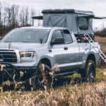 A truck from a Lexington used truck dealership is being used to hold a tent.