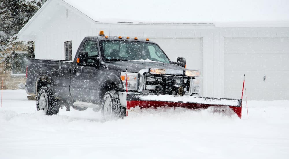 A black truck is being used to plow snow.