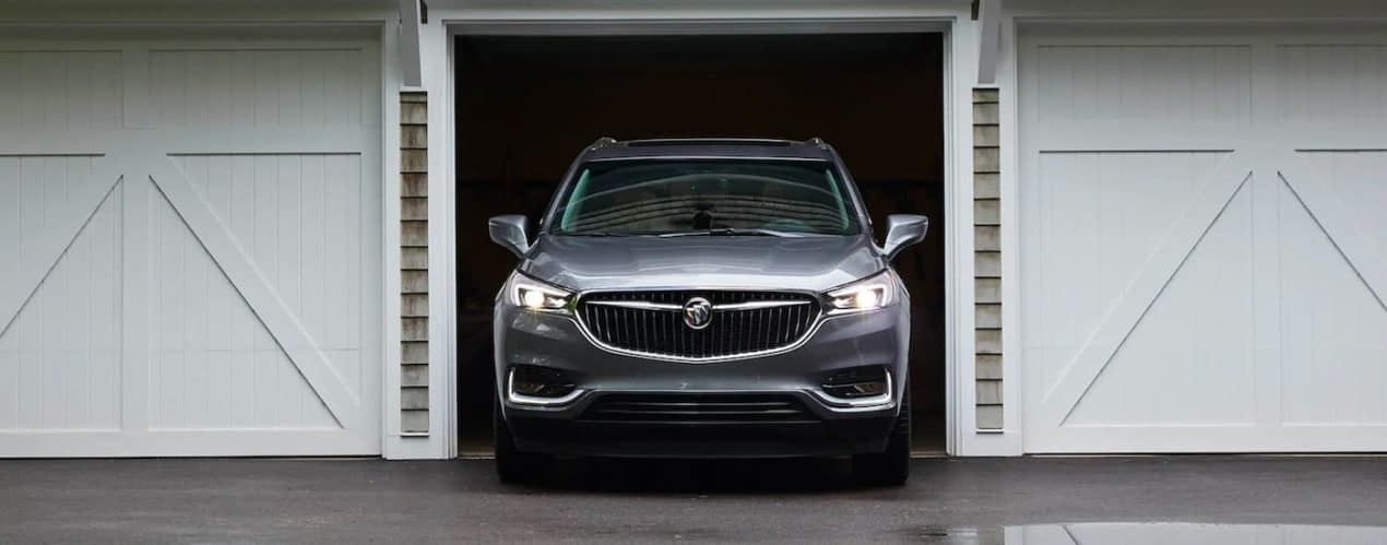 A grey 2021 Buick Enclave is shown front the front driving out of a garage.