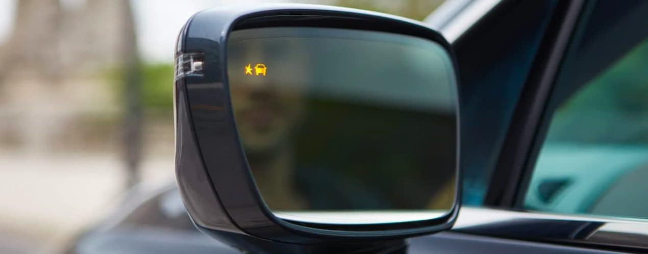 A close up shows the blind spot monitoring icon illuminated on the mirror of a black 2021 Buick Enclave.