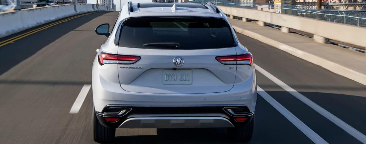 A white 2021 Buick Envision is shown from the rear driving on a bridge.