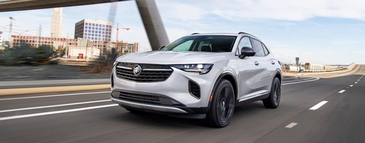 A white 2021 Buick Envision is shown from the side driving down a road after winning the 2021 Buick Envision vs 2021 Hyundai Santa Fe comparison.