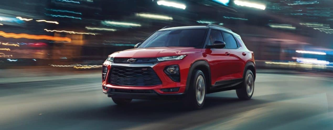 A red 2021 Chevy Trailblazer RS is shown driving past a blurred background.