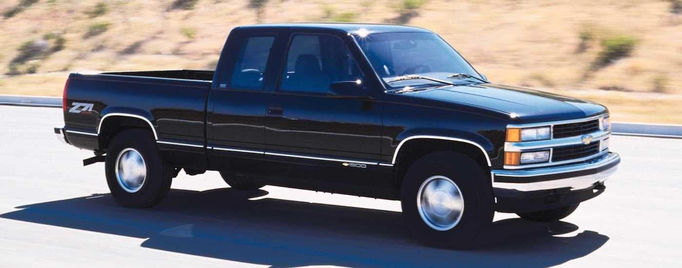 A black 1999 Chevy Silverado 1500 is shown from the side driving down a road after leaving a Lexington Silverado dealer.