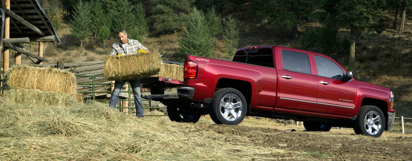 A red 2014 Chevy Silverado 1500 LTZ is shown from the side being loaded with hay.