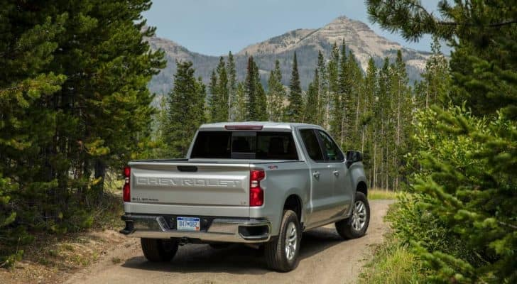A silver 2021 Chevy Silverado 1500 LT is shown from the rear parked on a dirt path with distant mountains.