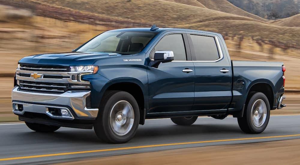 A blue 2021 Chevy Silverado 1500 is driving to a Lexington Silverado dealer.
