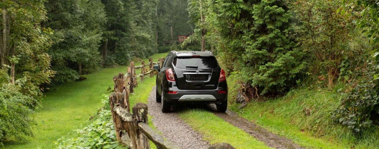 A black 2021 Buick Encore is shown from the back driving down a dirt and grass driveway.