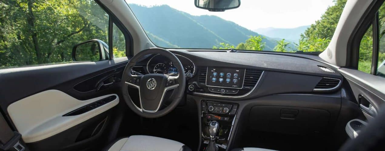 The interior of a 2021 Buick Encore shows the steering wheel and infotainment screen.