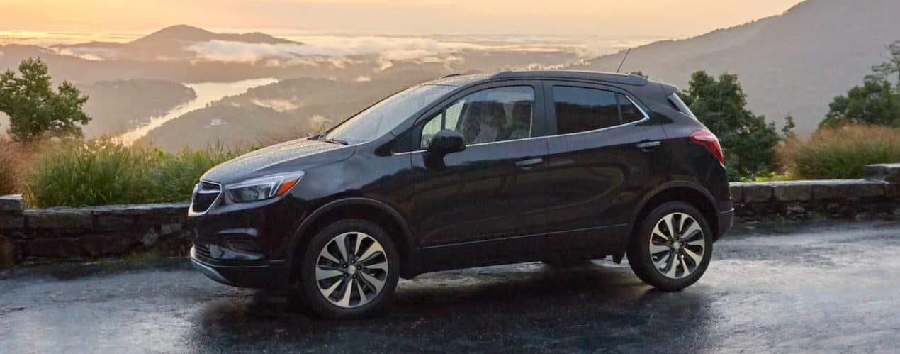 A blue 2021 Buick Encore is shown from the side parked at a lookout point during a 2021 Buick Encore vs 2021 Buick Encore GX comparison.