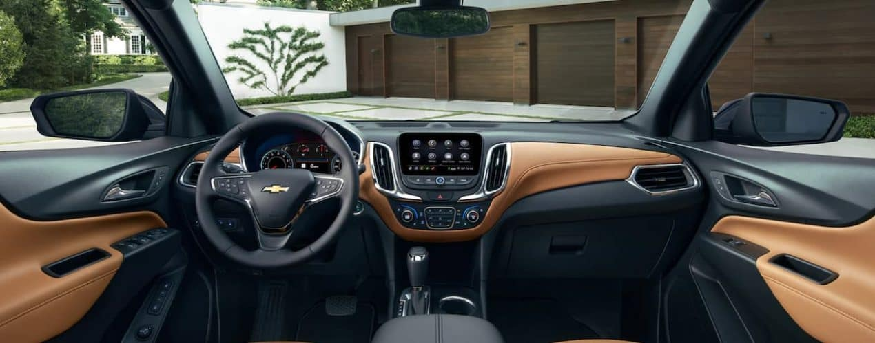 The interior of a 2021 Chevy Equinox shows the steering wheel and infotainment screen.