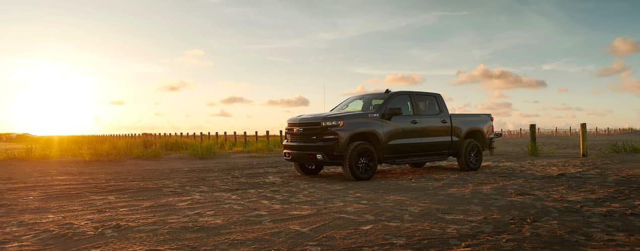 A black 2021 Chevy Silverado 1500 LT Z71 Trail Boss is shown from the side at sunset.