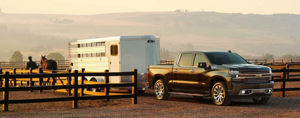 A black 2021 Chevy Silverado 1500 is shown towing a horse trailer through a fence.