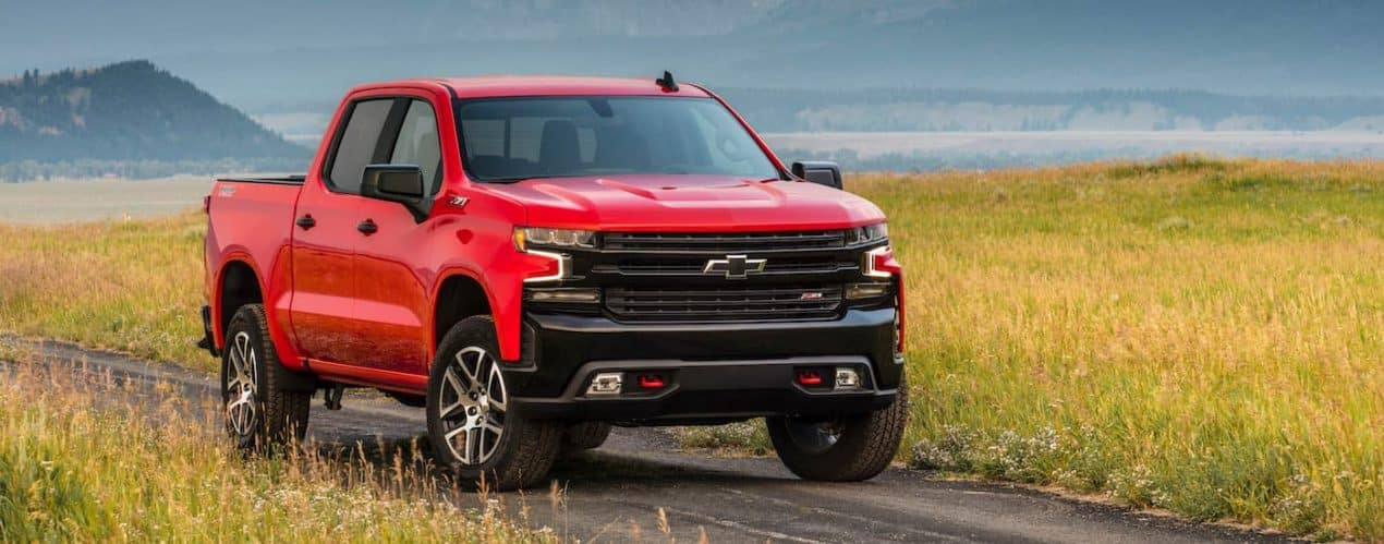 A red 2021 Chevy Silverado 1500 Z71 TrailBoss is parked on a dirt path next to a field.