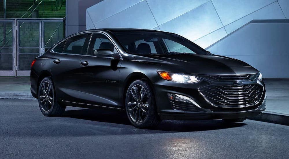 A black 2020 Chevy Malibu is parked in a modern gallery.