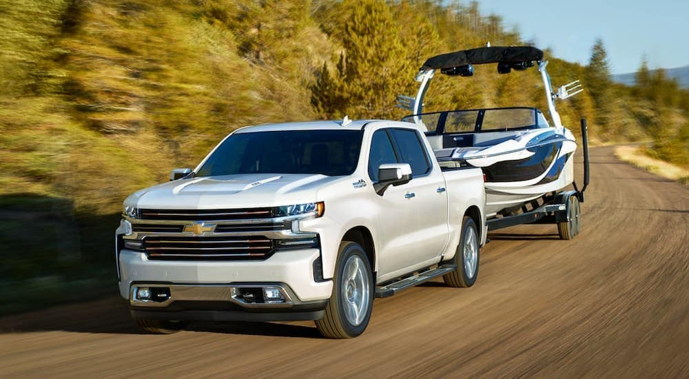 A white 2020 Chevy Silverado is towing a boat.