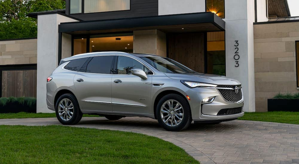 A silver 2022 Buick Enclave Avenir is shown parked in a driveway.