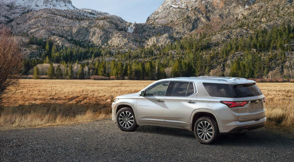 A silver 2022 Chevy Traverse Premium is parked near mountains.