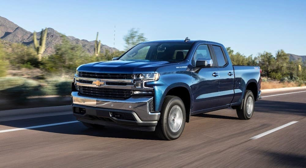 A blue 2019 Chevy Silverado 1500 is driving on a highway through a desert.