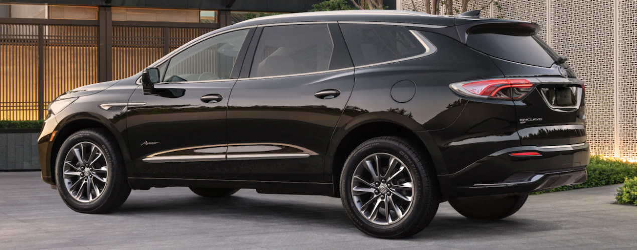 A black 2022 Buick Enclave is shown from the side parked in front of a modern house.