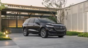 A black 2022 Buick Enclave is parked in front of a modern house.