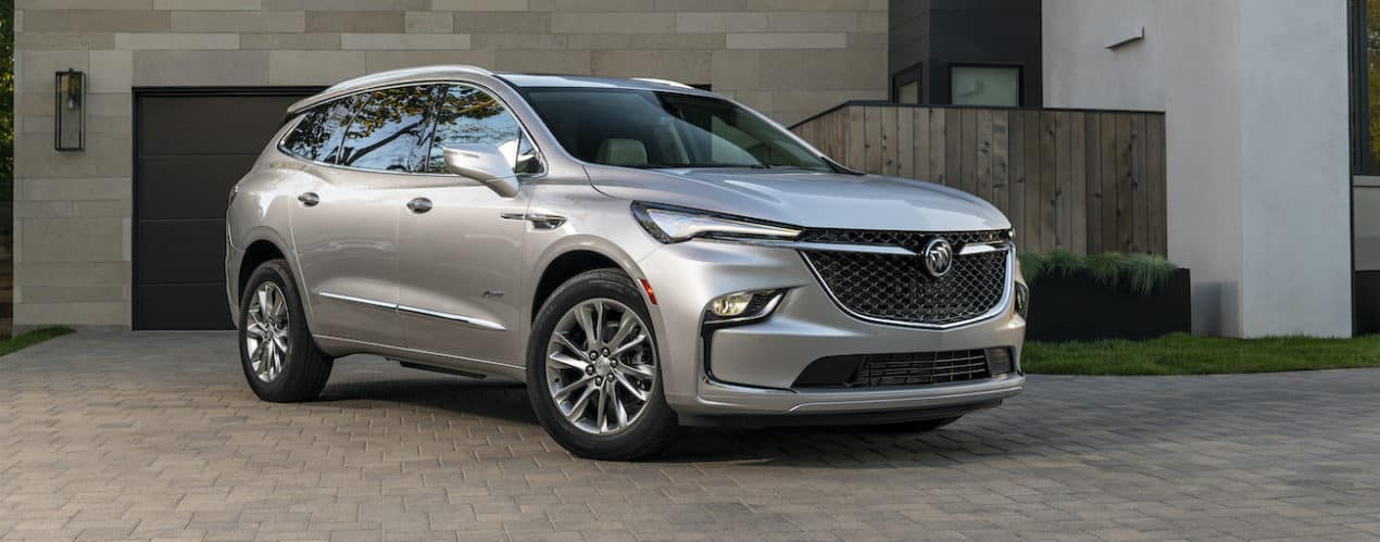 A silver 2022 Buick Enclave is parked in front of a modern house.