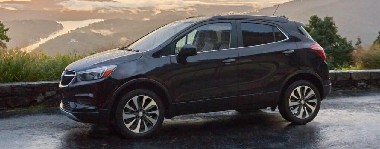 A black 2022 Buick Encore is shown from the side parked in the mountains.