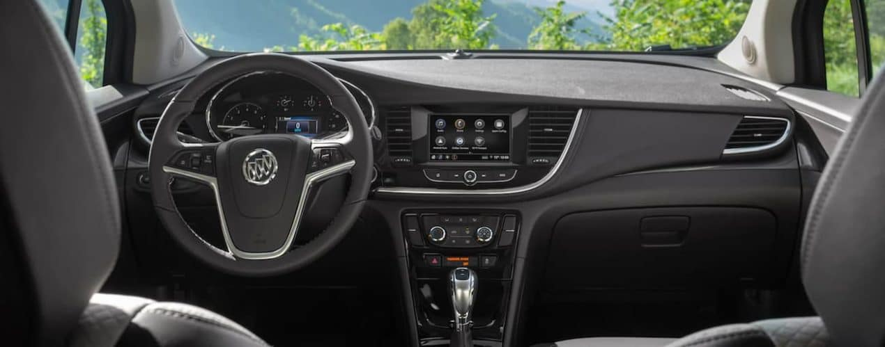 The black interior of a 2022 Buick Encore shows the steering wheel and infotainment screen.