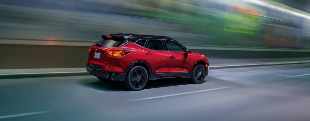 A red 2022 Chevy Blazer is driving down an open road.