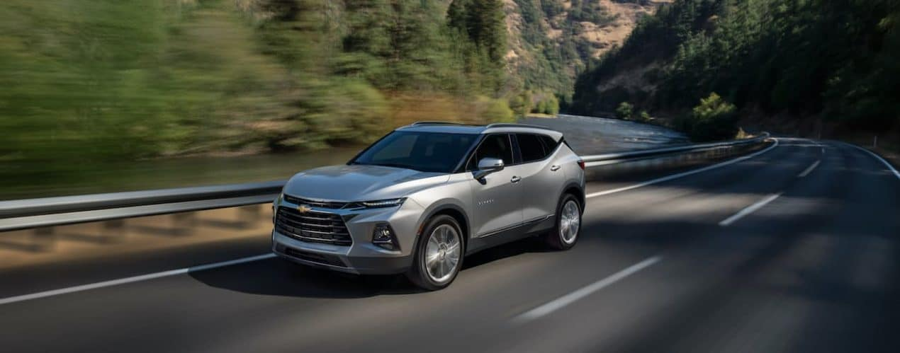 A silver 2022 Chevy Blazer is driving down a tree lined road.