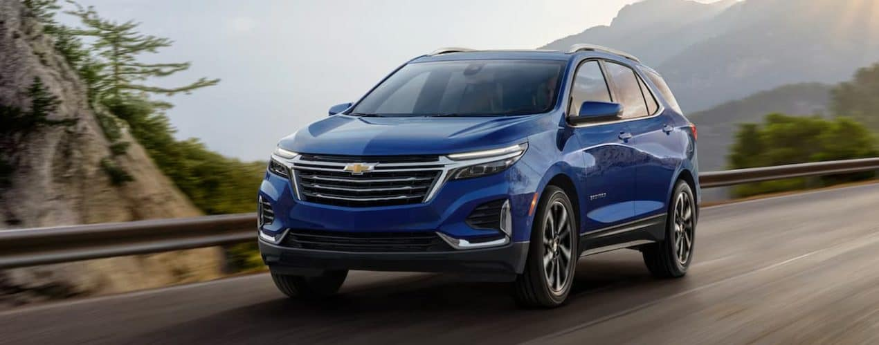 A blue 2022 Chevy Equinox is driving on an open road past a valley.