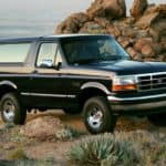 A black 1994 Ford Bronco XLT is shown parked with rocks in the background.
